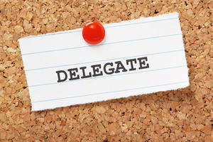 The word delegate on a bulletin board to remind you to outsource your blogging tasks