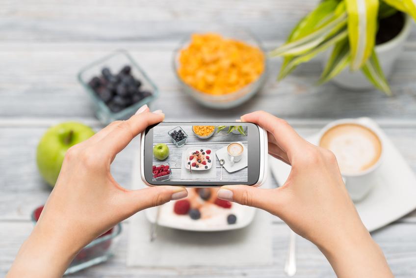 Woman taking a photo of breakfast with smartphone.